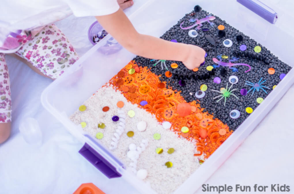 Halloween sensory bin showing a child playing with orange, purple and white rice and beans