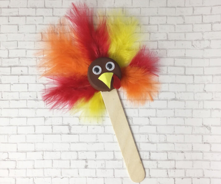 fun craft for kids featuring a turkey puppet with feathers