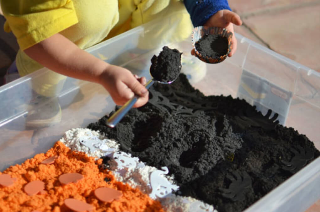 Toddler playing with Halloween orange and black cloud dough sensory bin