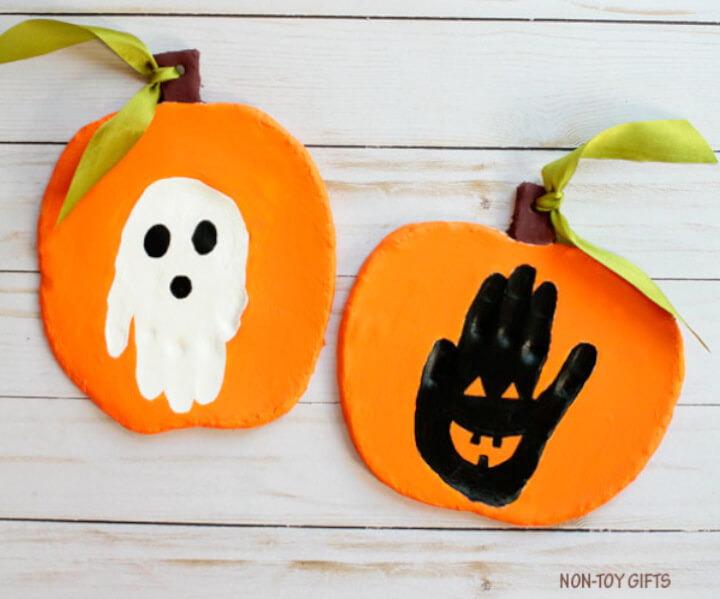 handprint Halloween keepsake craft for kids with a white ghost and black pumpkin