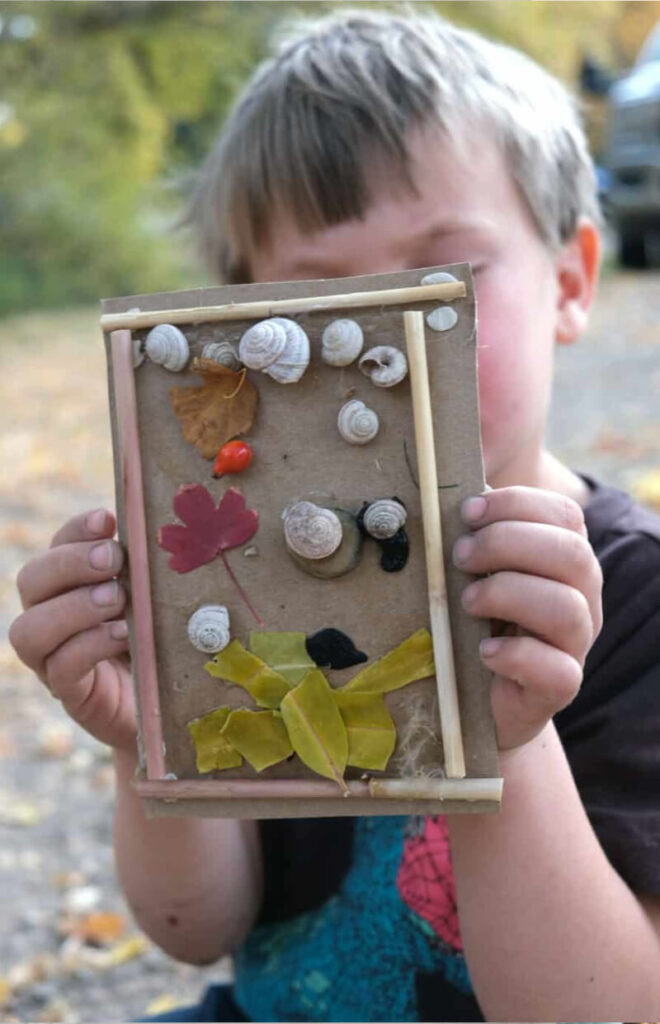 Children's DIY art project using natural elements featuring rocks, leaves and twigs.