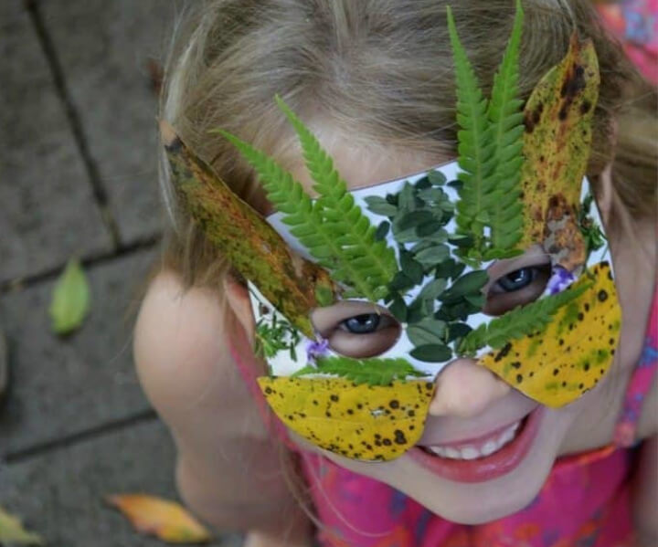 girl wearing a DIY mask made with leaves and flowers