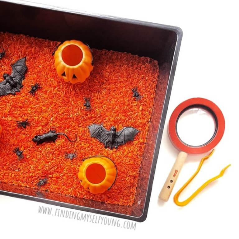 Spooky sensory tray featuring orange rice and creepy crawlies