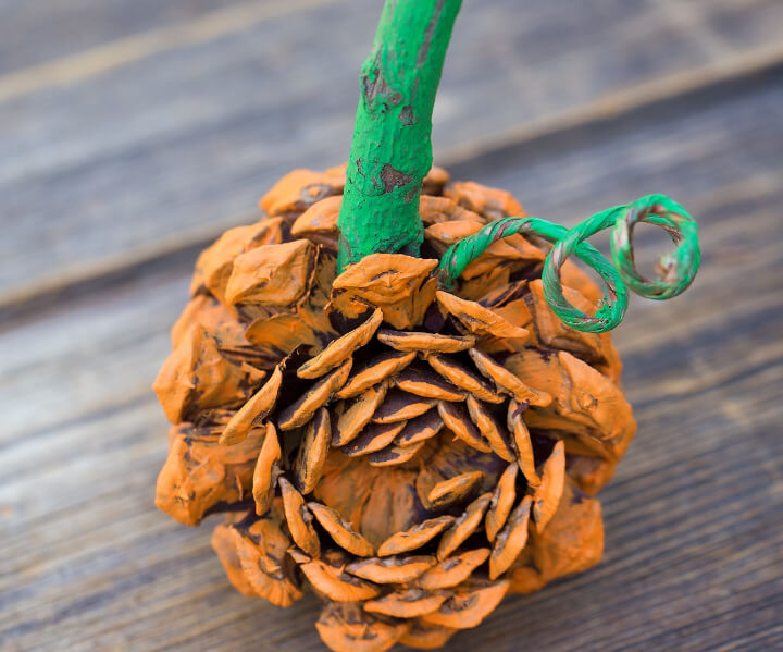DIY craft for kids of orange pumpkin made with pine cones