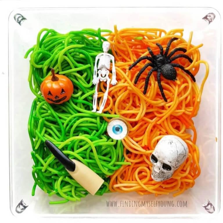 Halloween themed orange and green spaghetti sensory bin
