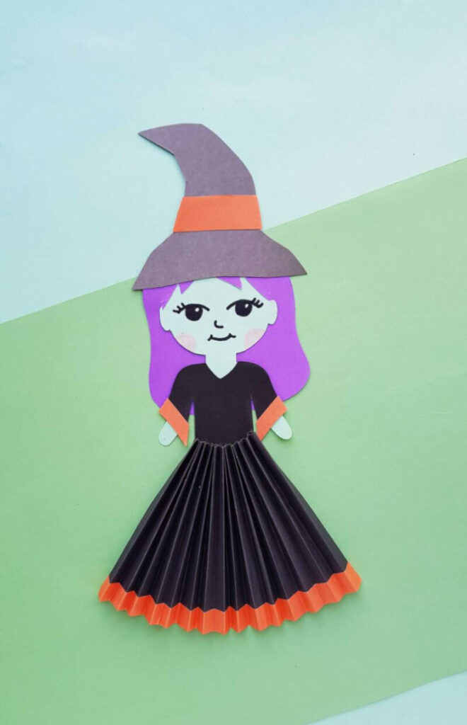Halloween witch craft for kids made with paper featuring an accordion skirt